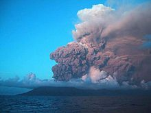 Plumes of ash and smoke billow from a volcano. Behind the plumes is blue sky. Water is in the foreground.
