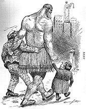 A political cartoon. A gigantic Samson-like figure is led towards a ballot box by a cigarette-smoking man in a checked suit and a tiny man reminiscent of a dwarf. Lady justice can be seen on a tall pillar in the background.