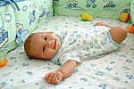 A smiling baby lying in a soft cot