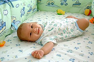 Infant bed - A baby lying on an elevated mattress in an infant bed with traditional crib bumpers