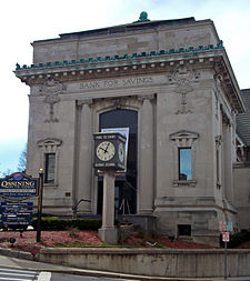 "A small square stone building with ornate decorative work, including the words ""Bank for Savings"". In front of it is a small clock tower with ""Time to enjoy Historic Ossining"" on it. At lower left is a sign welcoming visitors to the Ossining Central Business District."