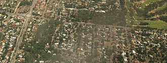 Banksia Park, South Australia - Aerial image of the northwestern part of Banksia Park, looking north. Hancock Road is the north-south road visible on the left-hand side of the image, and Grenfell Road is the east-west road. They intersect at the roundabout in the top-left hand corner. Banksia Park is the area southeast of the roundabout. The green region to the top right is part of Tea Tree Gully Golf Course.