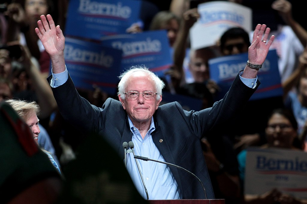 Bernie Sanders with arms raises in front of a crowd.