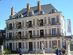 "photo of the front of the mansion that houses the French magic museum, ""La Maison de la Magie Robert-Houdin"". Large figures of crocodiles and a snake seem to be coming out of the open windows."