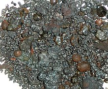 Dull, lustrous granules, pebbles and irregular blob-like lumps, most grey, a few brown.