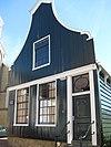 Houten huis met klokgevel (uit- en ingezwenkt voorschot) uit 19de eeuw en onderpui in Empirestijl, nu kosterij naast Nieuwendammerkerk