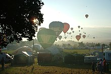 A large number of hot air balloons taking off from a field which is surrounded by tents and stalls. The sun is low in the sky and balloons can be seen flying into the distance.