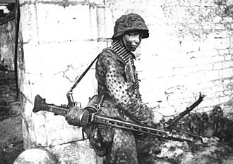 MG 42 - A German Waffen SS soldier involved in heavy fighting in and around the French town of Caen in mid-1944. He is carrying an MG 42 configured as a light support weapon with a folding bipod and detachable 50-round belt drum container.