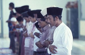 Islam Nusantara - Indonesian Muslim men wearing peci and sarung standing in prayer.