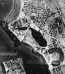 A black and white aerial photograph of an urban area by the sea with a water-filled, torus-shaped inlet.