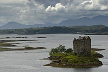 A small castle constructed as a four storey tower with a complex system of sloping and turreted roofs sits on a small islet. The island is grass covered with a few small trees in leaf on the far side. There is an array of other islets and rocks nearby in a wide body of water, beyond which is a forested peninsula. Dark mountains under a stormy sky can be seen in the distance.