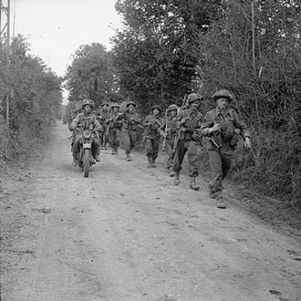 Army Reserve (United Kingdom) - A motorcycle and infantry of the 2nd Battalion, Glasgow Highlanders, 46th Infantry Brigade, 15th (Scottish) Infantry Division, advance along a lane near Caumont, 30 July 1944.