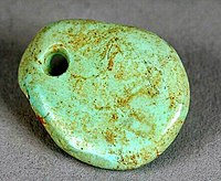 A small oval pieced of turquois with a hole drilled though the top