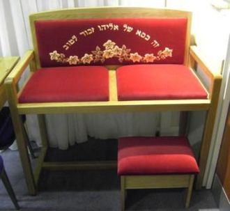 """Chair of Elijah"" used during the brit milah (circumcision) ceremony. The Hebrew inscription reads ""This is the chair of Elijah, remembered for Good."" Chair of Elijah.JPG"