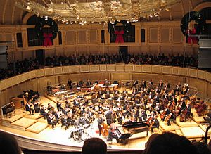 String section - The Chicago Symphony Orchestra performing with a jazz group. The string sections are at the front of the orchestra, arrayed in a semicircle around the conductor's podium.