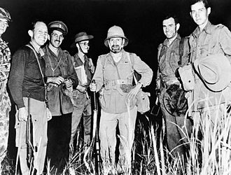 """Mike Calvert - Brigadier Calvert, third from left, with Orde Wingate (centre) and other Chindits at the """"Broadway"""" airfield in Burma awaiting a night supply drop, 1944"""