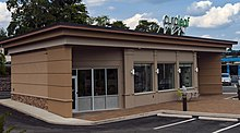 """A small tan concrete building with a flat roof and a green sign saying """"Curaleaf"""""""