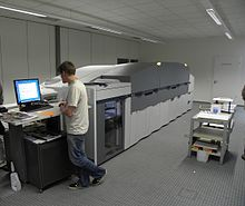 Photograph of a large, room-sized digital printer being operated.