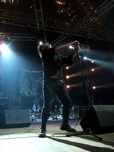Discharge performing in Rome in 2006. The distinctive lettering of the band's name can be seen in the banner at the back of the stage. Discharge2.jpg
