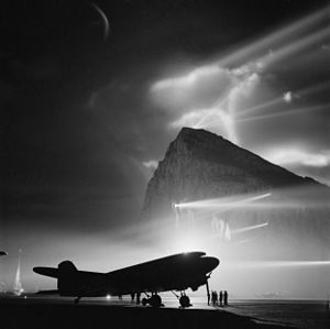 Gibraltar - During the Second World War, a Douglas Dakota of BOAC is silhouetted at Gibraltar by the batteries of searchlights on the Rock, as crews prepare it for a night flight to the United Kingdom.