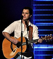 A young man with dark hair wearing a white shirt, playing a guitar and singing into a microphone