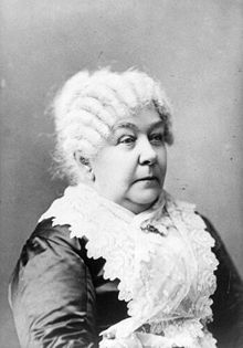 A monochrome photograph portrait of an elderly woman shown from the elbow up, turned somewhat to the right, a white lace apron covering a dark shiny fabric dress, the white hair in front-to-back rows of ringlets