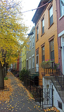 A long row of two-story, three-bay rowhouses in different colors seen looking down a city side street with trees in autumn color
