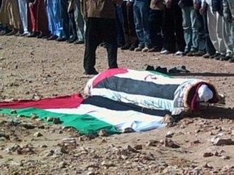Hamdi Lembarki - The remains of Hamdi Lembarki, covered with the Sahrawi Arab Democratic Republic flag, during his funeral in the outskirts of El Aaiun. Gdeim Izik (Western Sahara), 14 January 2006.