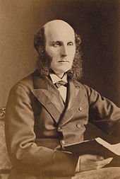 A well dressed middle aged man with a bald head and bushy sideburns, wearing a dark suit and carrying a large book