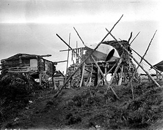 Egegik, Alaska - Dwellings of indigenous people on left and a bidarka (skin covered kayak) on a rack to the right in Egegik, ca. 1917