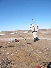 Geologist Katy Quinn of Crew 2 uses a sledge hammer to generate subsurface signals which will be detected by a geophone on Haynes Ridge on July 12, 2001.
