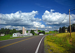 Country road with blue sky and clouds rolling overhead. There is a farm on the left and a sign indicating an intersection on the right.