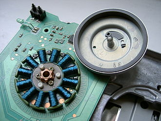 """Brushless DC electric motor - The motor from a 3.5"""" floppy disk drive. The coils, arranged radially, are made from copper wire coated with blue insulation. The rotor (upper right) has been removed and turned upside-down. The grey ring inside its cup is a permanent magnet."""