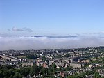 Fog in the Tay estuary. This view south from the summit of Dundee law shows a temperature inversion in the river estuary. Normally it is possible to see across the river to Fife. On this June morning cold air had crept from the sea into the river mouth (not an uncommon event especially in summer when sea haar spoils many a fine day in Dundee) and only a tiny fragment of Fife is visible above it.