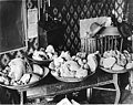 Four pans filled with gold nuggets on a table, Alaska, circa 1907 (AL+CA 2405).jpg
