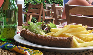 Frikandel - A frikandel with fries, lettuce and mayonnaise
