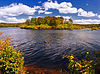 A sunny lake with an island and shore covered in autumnal foliage under a blue sky with some clouds