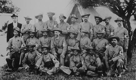 Stretcher-bearers of the Indian Ambulance Corps during the war, including the future leader Mohandas Karamchand Gandhi (Middle row, 5th from left) Gandhi Boer War.jpg