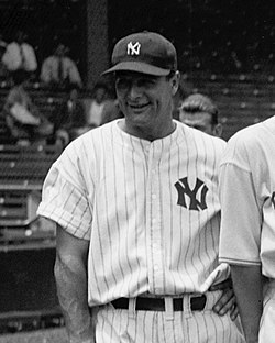 "A smiling man in a dark cap and white pinstriped baseball uniform with an interlocked ""N"" and ""Y"" on the left breast."