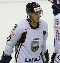 An ice hockey player standing, looking to the right of the camera. He is wearing a black helmet and a white uniform.