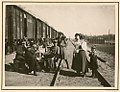 German officers conversing with women and child in rail yard (8672042109).jpg
