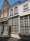foto van Klein huis waarvan de onderpui wordt gevormd door een kozijn dat de deur met bovenlicht en twee vensters omvat (eerste kwart 19e eeuw); de verdieping gebosseerd grijsgepleisterd, vensters met afgeronde bovenhoeken en stuckuiven. Schilddak met rode pannen