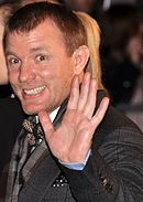 Guy Ritchie smiling and waving his hand