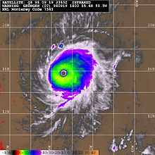 Multicolored satellite image of hurricane, with a clear eye at its center.