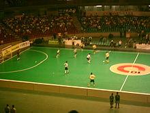 Photo des gradins d'une salle de sport où se joue une partie de futsal.