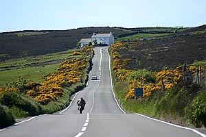 Kate's Cottage, Isle of Man - Kate's Cottage, looking in the opposite direction of a lap of the TT course (vehicles shown on left side of road are going north) with Creg-ny-Baa behind the camera position
