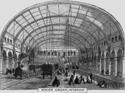 A railway station with a train pulled by an early steam engine. Brick walls rise on both sides and a glass roof arches overhead