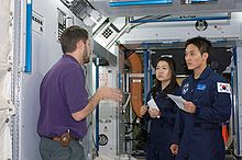 Yi So-yeon and Ko San participate in a space station hardware training session in the Space Vehicle Mockup Facility at the Johnson Space Center by Crew Systems instructor Glenn Johnson.