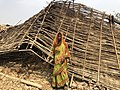 Lady stand in front of her destroyed house.jpg