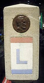 The Lincoln Highway was marked with small concrete obelisks.  Towards the top of the marker was a profile of Abraham Lincoln.  Below the profile, the route is marked with an L painted in red, white, and blue, the colors of the Lincoln Highway.